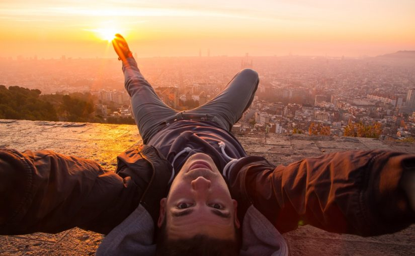 Taking a selfie from the Turo de la Rovira bunkers a hill with the best views of Barcelona city with the moment of the sunrise over the mediterranean sea with Barcelona city with his main landmarks.